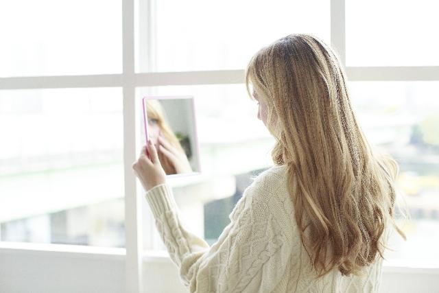 自分の顔を鏡で見ている女性